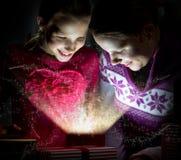 Zwei nette Mädchen, die innerhalb eines magischen Geschenkes schauen Stockfotografie