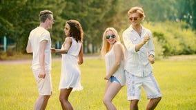 Zwei nette Paare, die heraus am Freiluftfestival, tanzend zur Musik hängen und haben Spaß stockfotos