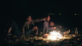 Zwei nette Paare, die sich umfassen und spät durch das Feuer nachts die Sterne betrachtend sitzen stock footage