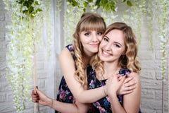Zwei nette Schwestern mit dem blonden Haar und den Blumen herum Stockfotos
