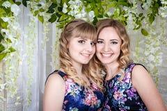 Zwei nette Schwestern mit dem blonden Haar und den Blumen herum Stockbild