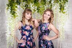 Zwei nette Schwestern mit dem blonden Haar und den Blumen herum Stockfoto