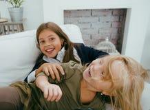 Zwei nette Schwestern zu Hause, die, kleines Mädchen im Hausinnenraum auf Sofa, das Haar verwirrend spielen und kämpfen mit Kisse Lizenzfreie Stockfotografie