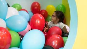 Zwei nette sprechende Mädchen beim Spielen mit mehrfarbigen Ballonen Lizenzfreie Stockfotografie