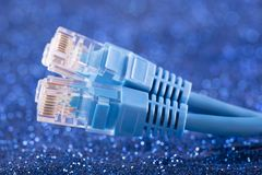 Zwei Netzkabel über blauem Scheinhintergrund lizenzfreie stockfotografie