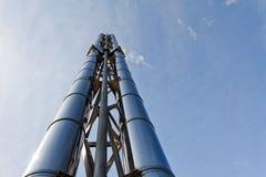 Zwei (2) neue glänzende Schornsteine steigen oben in den blauen Himmel Lizenzfreie Stockfotografie