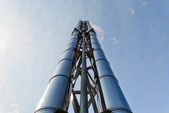 Zwei (2) neue glänzende Schornsteine steigen oben in den blauen Himmel Stockbilder