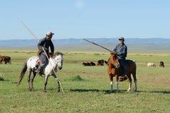 Zwei nicht identifizierte mongolische Männer, welche die traditionellen Kostüme fahren auf Pferdefreche antwort in einer Steppe i lizenzfreie stockfotografie