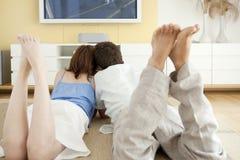 Zwei niederlegend auf dem Fußboden, der Fernsieht Stockbild