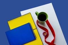 Zwei Notizbücher und eine Tasse Tee auf einem weißen und blauen Hintergrund lizenzfreies stockfoto