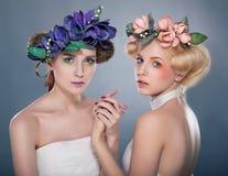 Zwei Nymphen in den Wreaths - hübscher Brunette und Blondine Stockfoto