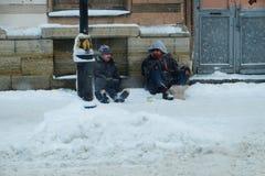zwei Obdachloser sitzt auf einer der Straßen während der Schneefälle Lizenzfreie Stockfotos
