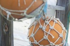 Zwei orange Bojen in den Netzen, die am Geländer hängen Lizenzfreie Stockbilder