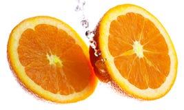 Zwei orange Hälften gespritzt mit Wasser Stockbild