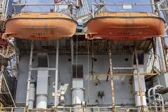 Zwei orange Rettungsboote, die am rostigen Containerschiff hängen stockfotografie