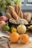 Zwei Orangen auf einer hölzernen Platte und einer Frucht sind der Hintergrund Lizenzfreies Stockbild