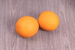 Zwei Orangen auf h?lzernem strukturiertem Hintergrund stockfotos
