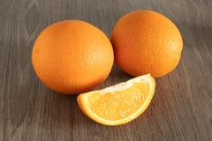 Zwei Orangen nahe bei ihnen ist eine Scheibe des Schnittes auf einem h?lzernen Hintergrund stockbilder
