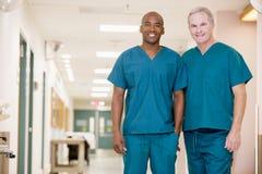 Zwei Ordonanzen, die in einem Krankenhaus-Flur stehen lizenzfreies stockbild