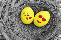 Zwei Ostereier gemalt mit emojis in der Liebe, gelegt in ein Nest Stockfotografie