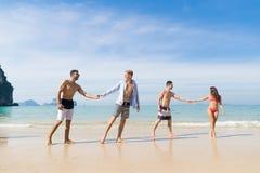 Zwei Paare auf Strand-Sommer-Ferien, junge Leute in der Liebe gehend, Mann-Frauen-Händchenhalten-Seeozean Stockfotos