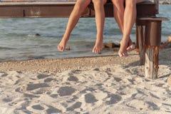 zwei Paare Beine, die über dem Strandsand baumeln lizenzfreie stockfotografie