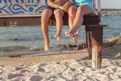 zwei Paare Beine, die über dem Strandsand baumeln stockbild