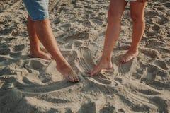 Zwei Paare Beine zeichnen auf die Sandzahlen lizenzfreies stockfoto