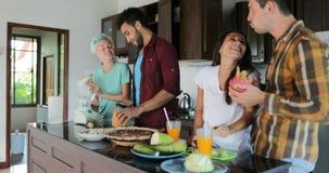 Zwei Paare in der Küche, die zusammen kochen, in der jungen Frau und in Man Group, die geschnittenes Gemüse und Früchte spricht,  stock video footage