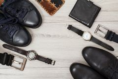 Zwei Paare der schwarzen ledernen Männer \ 's-Schuhe, Gurte für Männer, Geldbörsen und Uhren auf grauem Hintergrund lizenzfreie stockfotografie