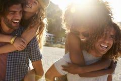 Zwei Paare, die auf dem Strand, hintergrundbeleuchtetes, nahes hohes, Ibiza trinken Lizenzfreies Stockbild