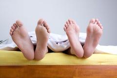 Zwei Paare Füße im Bett Stockfotografie