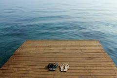 Zwei Paare Flipflops auf hölzerner Plattform nahe Küste Lizenzfreies Stockfoto