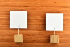 Zwei Papieranmerkungen mit hölzernen Haltern auf hölzernem Hintergrund Stockfotografie