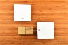 Zwei Papieranmerkungen mit verschiedenen Richtungen der hölzernen Halter auf Holz Stockfotos