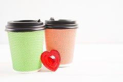 Zwei Papierschalen - rot und grün mit Herzen zwischen ihnen lizenzfreie stockfotos