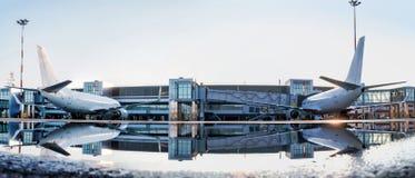 Zwei Passagierflugzeuge geparkt zu einer Jet-Brücke mit Reflexion I lizenzfreie stockbilder