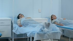 Zwei Patientinnen auf den Tropfenfängern, die auf Betten in der Krankenstation überprüft wird von zwei Doktoren liegen stock video
