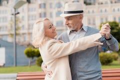 Zwei Pensionäre tanzen auf das Quadrat nahe der Bank Sie sind glücklich Stockbilder