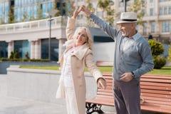 Zwei Pensionäre tanzen auf das Quadrat nahe der Bank Sie sind glücklich Stockfoto