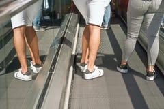 Zwei Personen fahren herauf eine Rolltreppe, nur die Beine sichtbar sind, die linke Person wird widergespiegelt im Glasdeckel lizenzfreie stockfotos