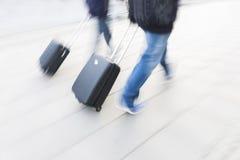 Zwei Personen mit kleinen schwarzen Koffern Stockfotografie