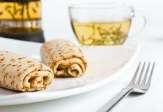 Zwei Pfannkuchenrollen mit einer Tasse Tee stockfotos