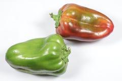 Zwei Pfeffer, rot und grün, auf weißem Hintergrund Lizenzfreie Stockfotos