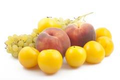 Zwei Pfirsiche, Pflaumen und Trauben breiten sich auf Weiß aus Stockbild