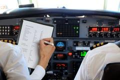 Zwei Piloten in den Flugzeugen mit Checkliste Stockfotografie