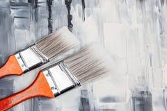 Zwei Pinsel auf künstlerischem Segeltuch lizenzfreie stockbilder