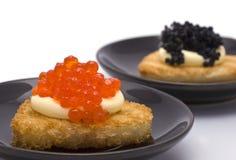 Zwei Plättchen mit Herz-förmigen Toast mit Kaviar Stockbilder