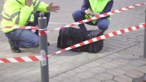 Zwei Polizei Sappers nahe bei einem gefährlichen Gegenstand, Taschenbombenangriff auf der Straße stock footage