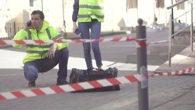 Zwei Polizeibeamten nahe bei einem gefährlichen Gegenstand, Taschenbombenangriff stock video